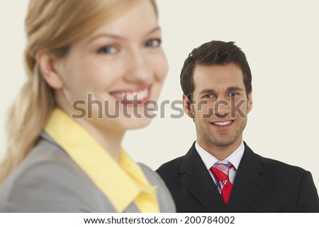 Businesswoman smiling, man standing in background - stock photo
