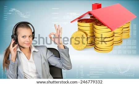 Businesswoman smiling sitting in office chair wearing headset making okay gesture with both hands. Piles of golden dollars under roof beside. Hi-tech charts with various data as backdrop - stock photo
