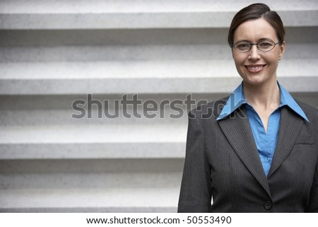 Businesswoman smiling, standing in front of wall, portrait - stock photo