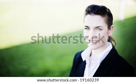 businesswoman smiling while wearing a business suit standing outside in the grass and sunshine - stock photo