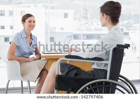 Businesswoman speaking with disabled colleague at desk in office - stock photo