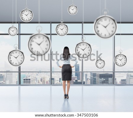 Businesswoman standing and looking into the window, back view, several models of pocket watches hovering in the air. A concept of a value of time in business. New York panoramic view.