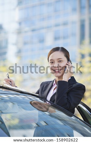 Businesswoman standing by car and using phone