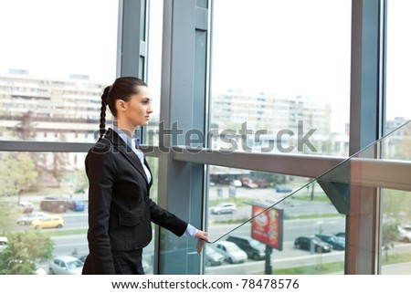 businesswoman standing in a futuristic office building, looking outside - stock photo