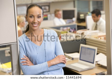 Businesswoman standing in cubicle smiling - stock photo