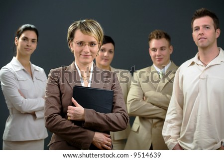 Businesswoman standing in front of his smiling team.