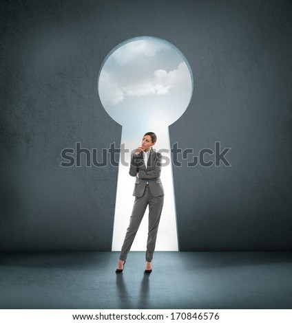 Businesswoman standing in front of opened concrete wall - stock photo
