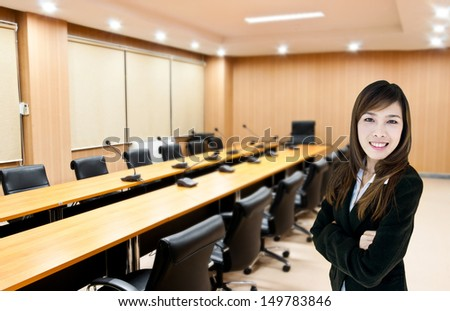 businesswoman standing in meeting room - stock photo