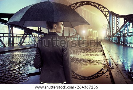Businesswoman standing in the rain - stock photo