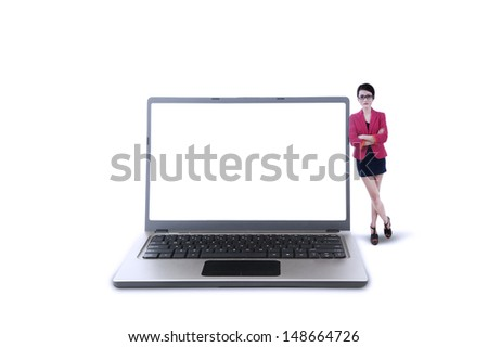 Businesswoman standing next to laptop on white background