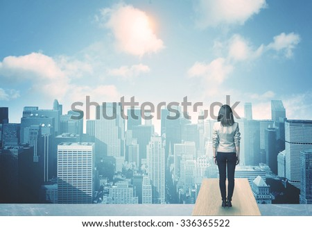 Businesswoman standing on a roof and looking at future city - stock photo