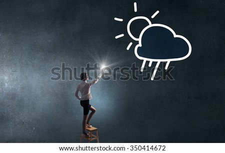 Businesswoman standing on chair and reaching cloud in sky