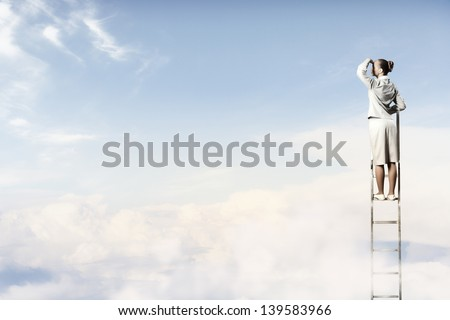 Businesswoman standing on ladder looking into distance against cloudy background - stock photo
