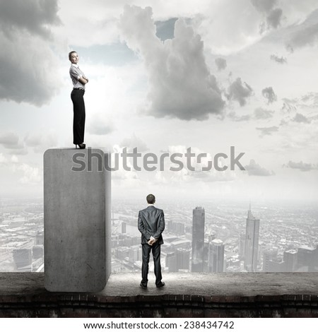 Businesswoman standing on top and looking down at colleague - stock photo