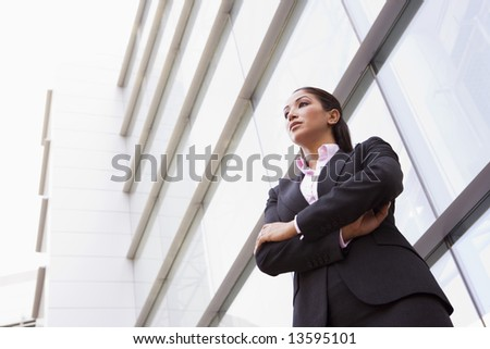 Businesswoman standing outside modern office building - stock photo