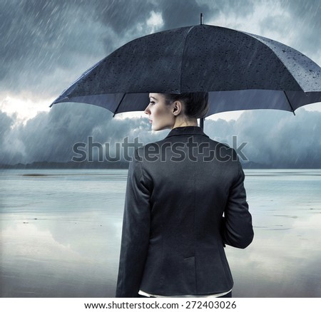 Businesswoman standing with an umbrella - stock photo