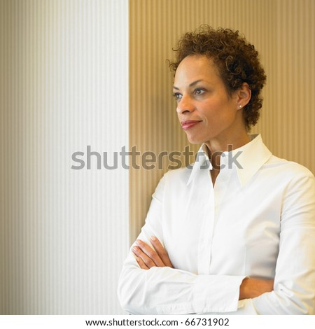 Businesswoman standing with arms crossed - stock photo
