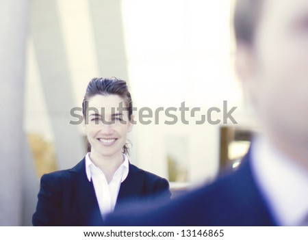 businesswoman standing with arms crossed directly behind businessman - stock photo