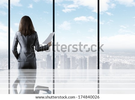 Businesswoman standing with back against office window holding documents in hand - stock photo
