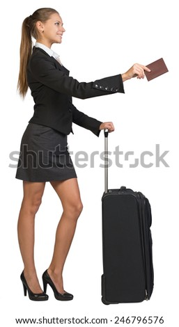 Businesswoman standing with wheeled travel bag, handing passport with blank cover, smiling. Isolated over white background - stock photo