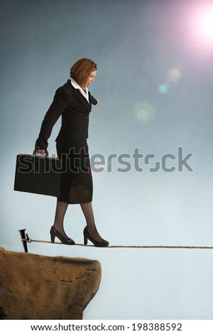 businesswoman starting out on a highwire tightrope  - stock photo
