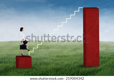 Businesswoman stepping up on the stair of business graph - stock photo