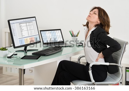 Businesswoman Suffering From Backache While Working In Office - stock photo