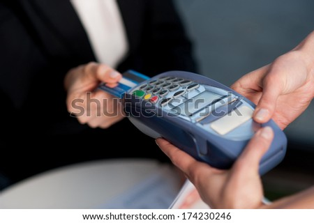 Businesswoman swipes her credit card to make the payment - stock photo
