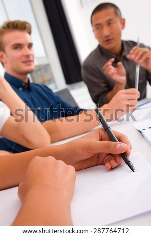 Businesswoman taking note in meeting - stock photo