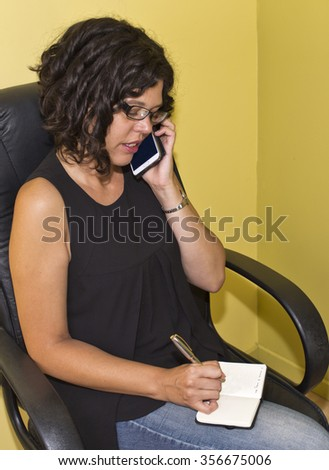 Businesswoman taking notes while on mobile phone - stock photo
