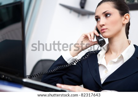 businesswoman taking telephone call in her office - stock photo