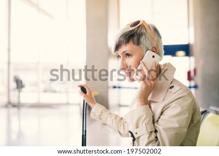 Businesswoman talking at mobile phone at Charles de Gaulle airport, Paris.  - stock photo