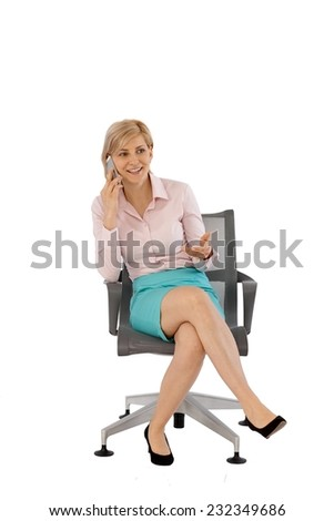 Businesswoman talking on mobilephone, sitting in swivel chair, smiling. Full size, white background. - stock photo