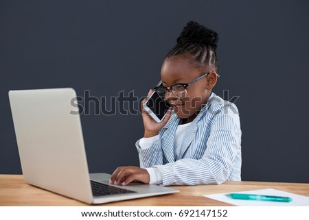 Businesswoman talking on smart phone while using laptop at desk in office