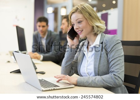 Businesswoman talking on the mobile phone in modern office - stock photo