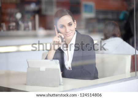 Businesswoman talking on the phone in a cafe - stock photo
