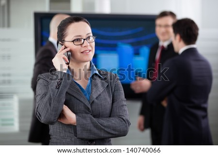 Businesswoman talking on the phone in the conference room. Colleagues in the background. - stock photo