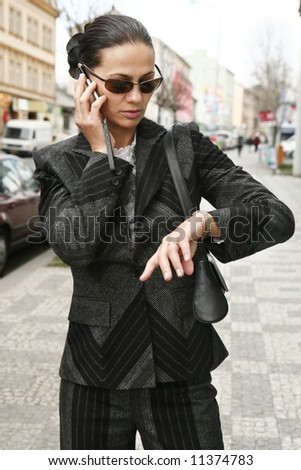 Businesswoman talking on the phone in the street - stock photo
