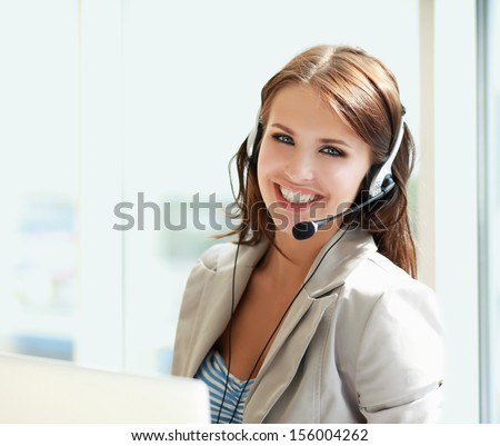 businesswoman talking on the phone while working on her computer at the office - stock photo