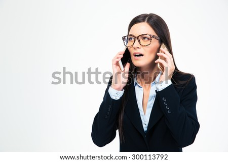 Businesswoman talking on two phones isolated on a white background - stock photo