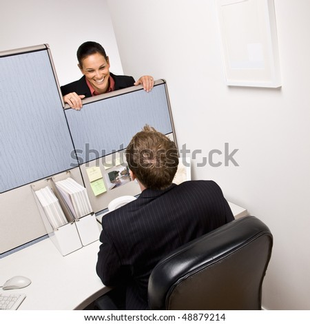 Businesswoman talking to co-worker in next cubicle - stock photo