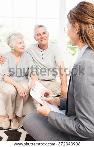 Businesswoman talking with senior couple and writing on clipboard at home - stock photo