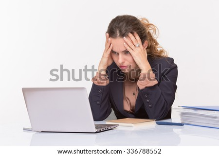 Businesswoman thinking about business strategies and looking at her laptop computer while working in the office.