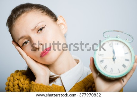 businesswoman tired and holding alarm clock isolated in the studio