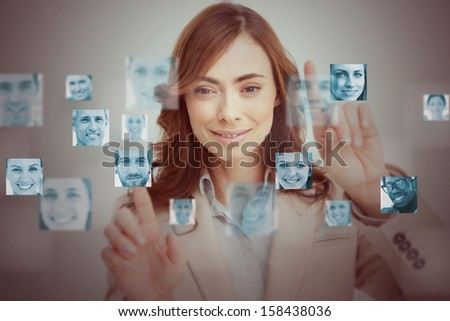 Businesswoman touching digital interface showing human faces - stock photo