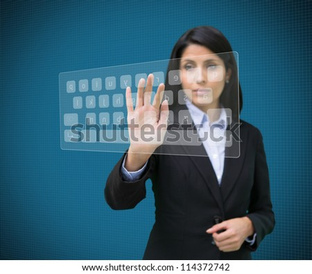 Businesswoman touching projected digital keyboard on blue