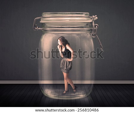 Businesswoman trapped into a glass jar concept on background - stock photo