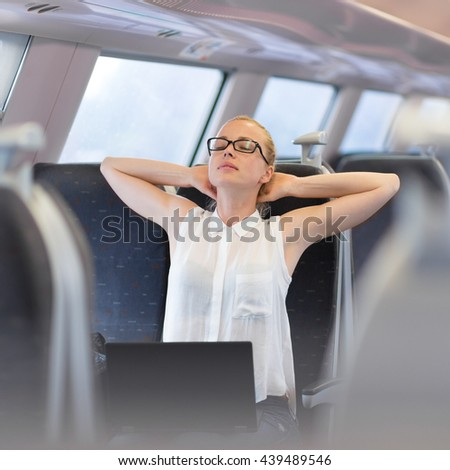 Businesswoman traveling by train, streching on her seat while working on laptop. Business travel concept. - stock photo