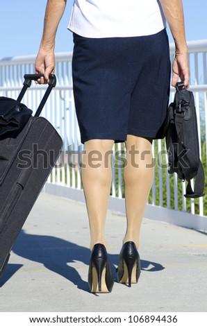 Businesswoman traveling with suitcase and laptop, wearing white blouse, dark skirt and high heel shoes. - stock photo