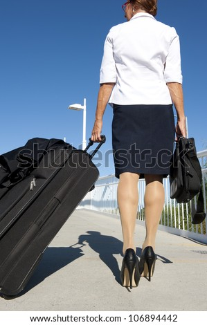 Businesswoman traveling with suitcase and laptop, wearing white blouse, dark skirt and high heel shoes, isolated with blue sky as background and copy space. - stock photo
